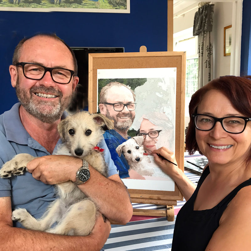a man and a woman painting a painting by numbers for adults picture of themselves and a puppy